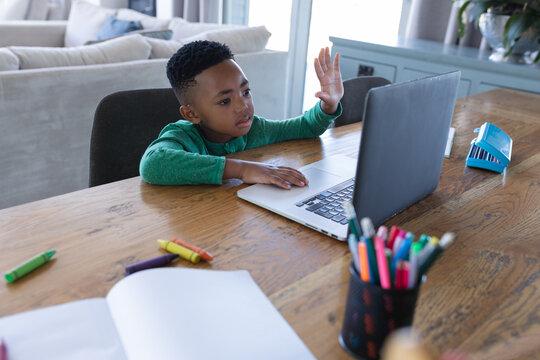 African american boy in online school class, using laptop