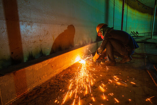 Male worker metal cutting spark on tank bottom steel plate with flash of cutting light close up wear protective gloves and mask