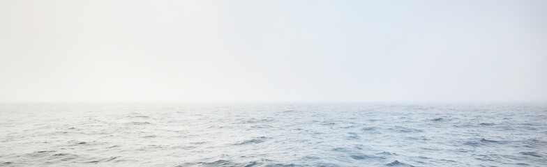 Baltic sea in a morning fog at sunrise, Sweden. View from a sailing boat. Soft golden sunlight,...