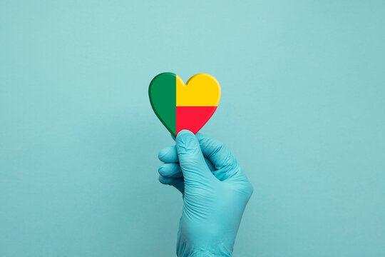 Hands wearing protective surgical gloves holding Benin flag heart
