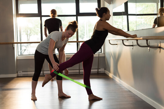 Two caucasian women using rubber tape, stretching, exercising in gym