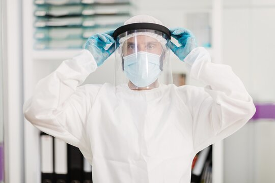 Positive male doctor with latex gloves and white uniform putting on face shield protective mask standing in modern medical office and looking at camera