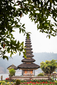 Exterior of Uluwatu Temple with ornamental roof located in blooming garden on Bali
