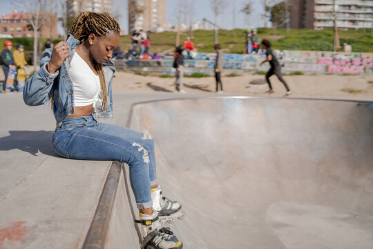Cool black female with braided hairstyle and in rollerblades sitting on ramp in skate park and looking down