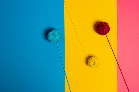 From above of small woolen thread balls representing lollies on sticks on blue, yellow and pink background