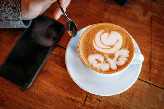 From above anonymous woman about to have coffee with a drawing of a flower in the coffee foam next to a smart phone