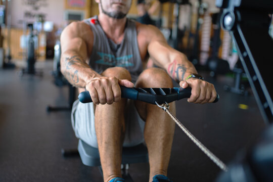 Crop muscular male athlete doing exercises on rowing machine during workout in gym