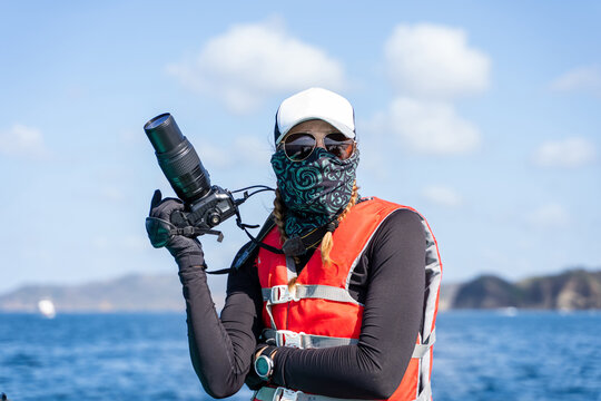 Front view of anonymous female traveler in life jacket and scarf with professional camera during trip