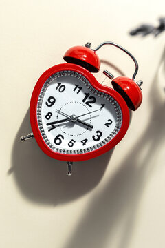 Red metal alarm clock in shape of heart placed on vibrant beige background in studio
