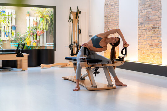 Focused fit female sitting on bench and stretching arms on pilates machine during training