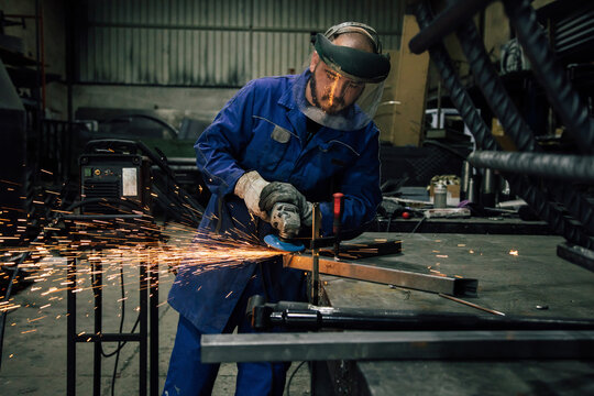 Workman in protective mask and blue workwear grinding metal part with angle grinder at workbench in professional garage