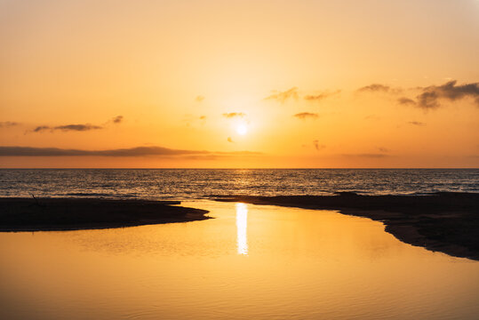 Scenic view of vivid orange sunset sky over calm sea water in evening
