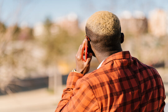 Back view of unrecognizable trendy black male with hair dyed blond in checkered suit and eyewear talking on mobile phone while looking away in sunlight