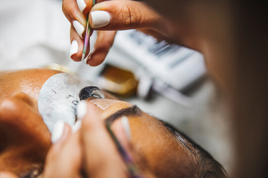 High angle of crop unrecognizable cosmetologist with tweezers applying fake eyelashes for extension on eye of ethnic client in salon