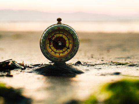 Selective focus of retro compass placed on sand against sea and mountains at sunset time