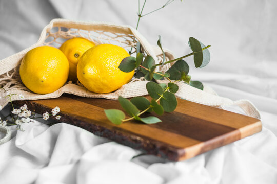 Colorful whole lemons in zero waste bag near wavy plant sprig on wooden chopping board on creased textile
