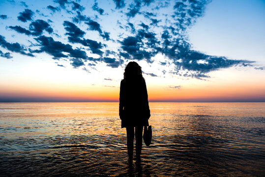 Back view of silhouette of unrecognizable female standing in water of sea and admiring spectacular view of colorful sundown sky in summer