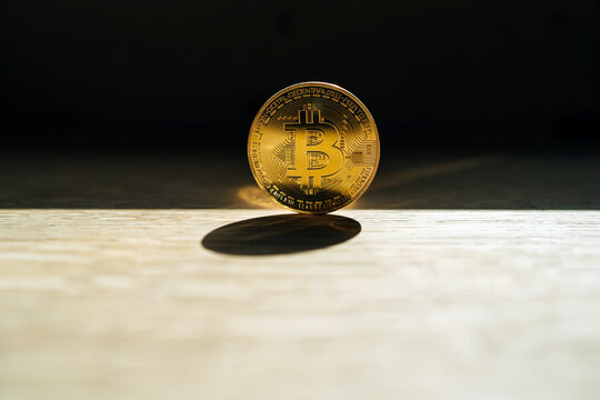 Metal coin with ornament and letter representing cryptocurrency symbol on desk with shade on dark background