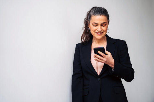 Delight middle aged female entrepreneur with ponytail wearing black suit text messaging on cellphone while standing on white background