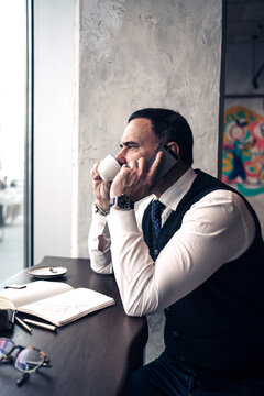 Side view of mature ethnic male entrepreneur talking on cellphone while drinking hot beverage and looking forward in cafeteria