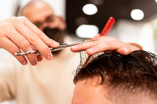 Male stylist trimming wet hair of crop anonymous client with scissors in hairdressing salon on blurred background