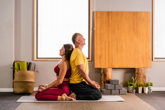 Side view of calm male and female instructors in activewear recreating in Thunderbolt asana on mat during yoga training together in studio