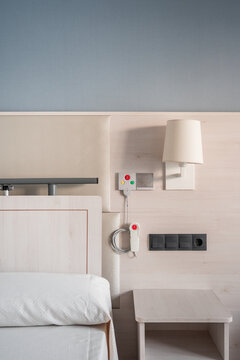 Nurse call system with emergency buttons installed near bed in minimalist medical room interior in hospital