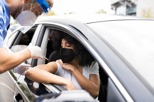 Side view of male doctor in protective uniform, latex gloves and face shield vaccinating African American female patient inside the car on a drive through mobile clinic during coronavirus outbreak