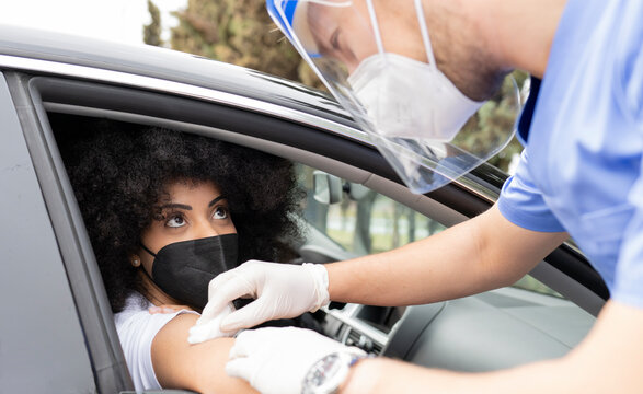 Male doctor in protective uniform, latex gloves and face shield disinfecting African American female patient arm with cotton and alcohol preparing to vaccinate inside the car on a drive through mobile clinic during coronavirus outbreak