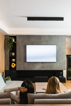 Back view of lesbian couple of unrecognizable women sitting on sofa in living room and watching movie on TV set while chilling at weekend at home