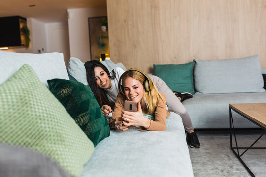 Couple of lesbian females lying on sofa and taking self shot on smartphone while chilling together in living room at weekend