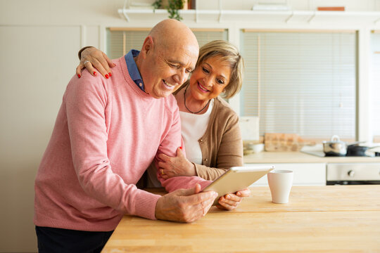 Middle aged woman talking to man using tablet while standing together in kitchen at home