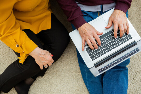 Top view of crop anonymous mature couple sitting on floor at home and browsing netbook together