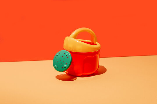 Colorful illustration representing plastic toy watering cans with colorful handle on orange background