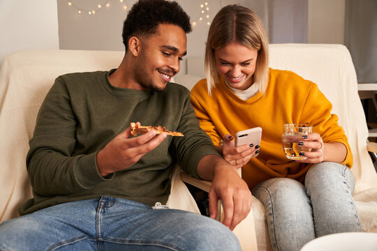 Content multiracial couple sitting in living room while eating pizza and watching funny video on smartphone at weekend