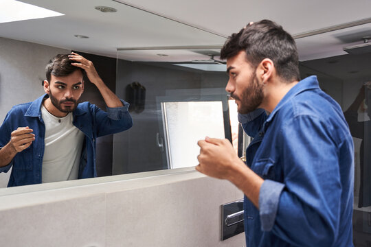 Side view of concentrated young bearded ethnic guy in stylish clothes touching hair while looking in mirror in modern bathroom