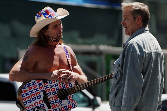 """Robert Burck, better known as the """"Naked Cowboy"""" speaks to a man in New York City"""