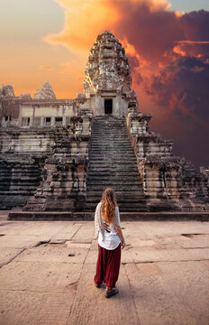 Back view of unrecognizable female tourist admiring old masonry worship exterior with staircase under cloudy sky at sundown in Cambodia
