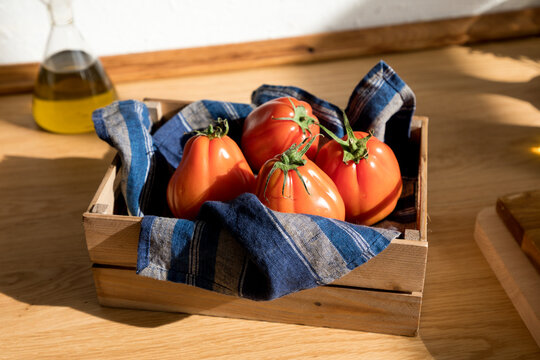 High angle of fresh ripe red tomatoes placed on natural wooden tray with napkin in home kitchen