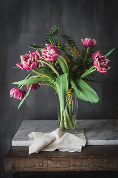 Blossoming pink flowers with gentle petals and green leaves in vase on gray background