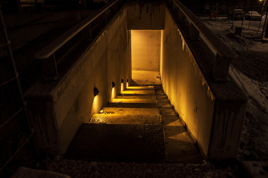 night picture of stairs leading to a cellar for bikes below a flat
