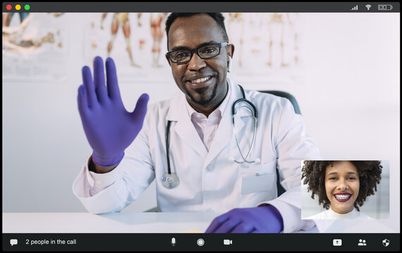 Positive African American male doctor in medical uniform and gloves waving hand and smiling while greeting ethnic female patient during video conference