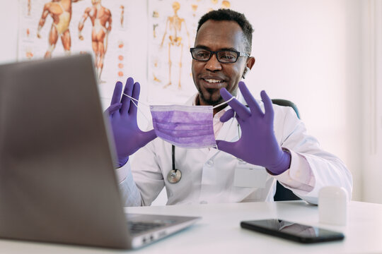 Positive adult African American male doctor in medical uniform and latex gloves smiling and showing mask while having video conference via laptop in modern hospital