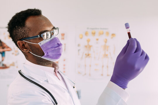 African American male doctor in medical glove demonstrating test tube with blood sample on white background