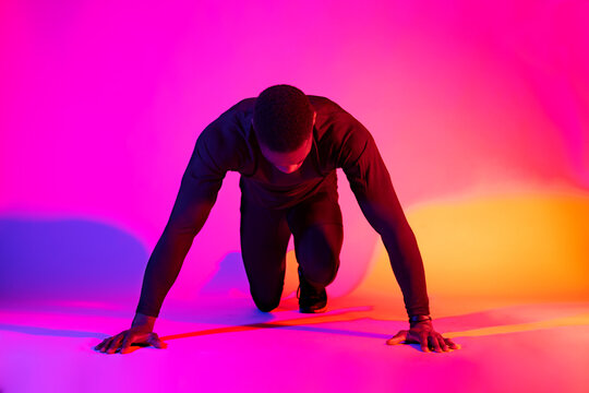Full length concentrated fit African American male runner standing in crouch start position and looking down on colorful background in studio