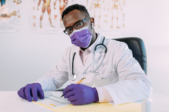 African American doctor in eyeglasses working while writing in patient file at table in hospital
