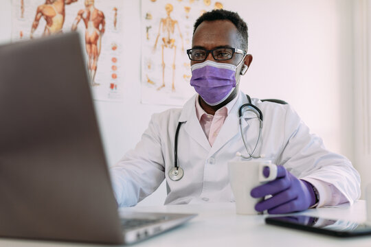 Unrecognizable concentrated African American male doctor in medical robe and mask drinking coffee and working on laptop in modern clinic