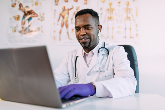 Concentrated young African American male physician in medical robe and TWS earphones working on laptop while sitting at table in modern clinic