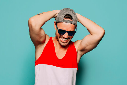 Cheerful young bearded ethnic guy wearing trendy casual striped shirt and cap with black sunglasses touching head and looking down on blue background