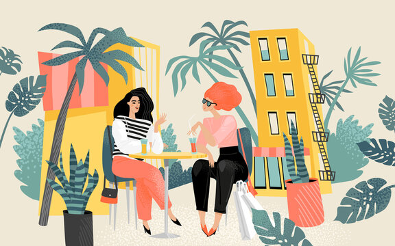 Two lovely girls sitting at a table in a summer cafe and chatting. City life